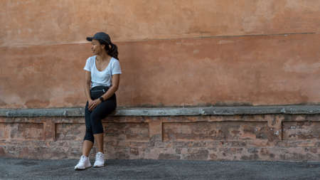 Woman in cap sitting on bench in front of beautiful teracota wall looking away from photographer in Bologna Italy