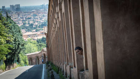 Teen with headband sticking her head out between columns of portico in Bologna Italy
