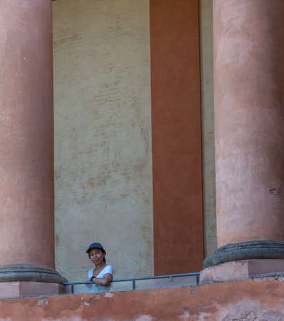 Asian woman in tshirt and hat standing on balcony between large columns in Bologna Italy 免版税图像