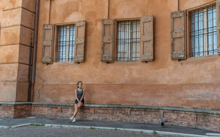 Young teen girl with headband, shorts, tanktop and sneakers sitting on brick bench under 3 windows with shutters and bars in Bologna Italy