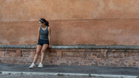 Young teen girl with headband, shorts, tanktop and sneakers sitting on brick bench in Bolgona Italy