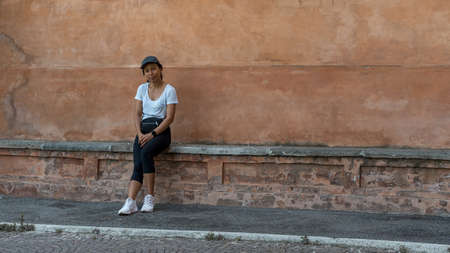 Woman in cap sitting on bench in front of beautiful teracota wall looking at photographer in Bologna Italy