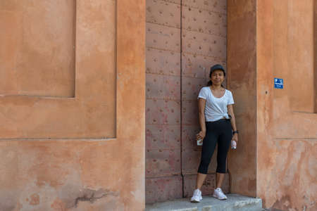 Woman in har, black pants, tshirt and sneakers holding phone in doorway in bologna Italy