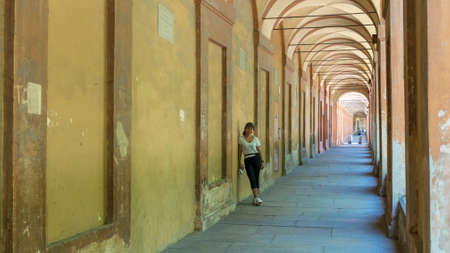 Asian woman in hat, tshirt and sneakers leaning against wall of portico in Bologna, Italy