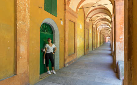 Woman in black pants holding thermos and standing in front of green door in portico in Bologna Italy 免版税图像