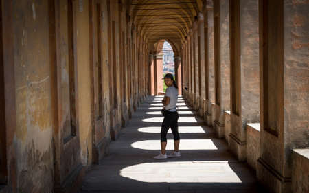Woman in hat standing in portico with shadows and looking back in Bologna Italy