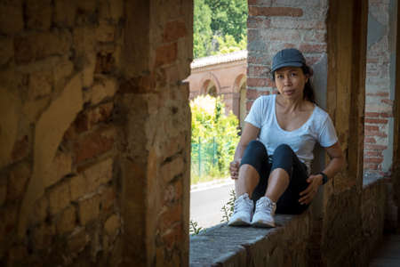 Woman in cap and sneakers sitting in window of portico looking at camera in Bologna Italy 免版税图像