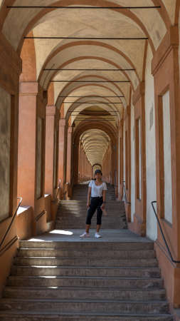 Asian woman in hat and sneakers standing in the middle of a stairway in a portico in Bologna Italy