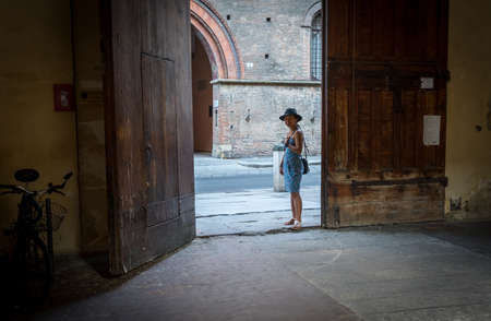 Asian woman in black hat and blue sundress standing by large brown wooden door of courtyard  with bicycle behind door in Bologna Italy