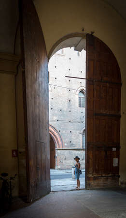 Asian woman in black hat and blue sundress standing by large brown wooden door of courtyard in Bologna Italy