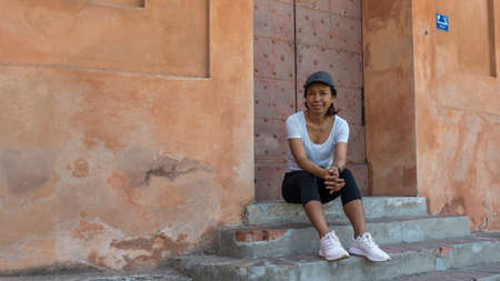 Woman sitting on steps in front of doorway with cap and sneakers in Bologna Italy looking at photographer