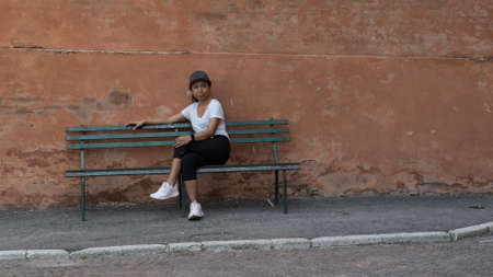 Woman in hat, tshirt, black pants and sneakers sitting on park bench with legs crossed in Bologna with another park bench to her right 免版税图像