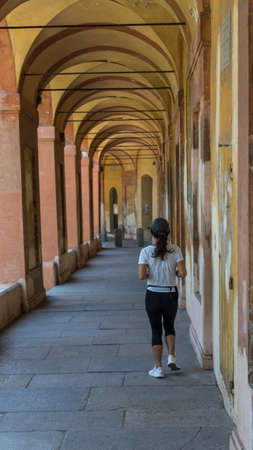 Woman running through long Portico in black pants and sneakers in Bologna, Italy 免版税图像