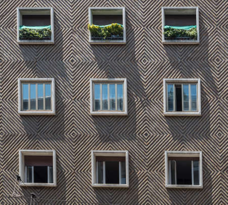 face of cement apartment building with 9 symmetrical windows in Bologna Italy