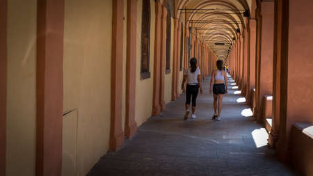 Mother and daughter walking through arched portico in a summer day in Bologna Italy 免版税图像