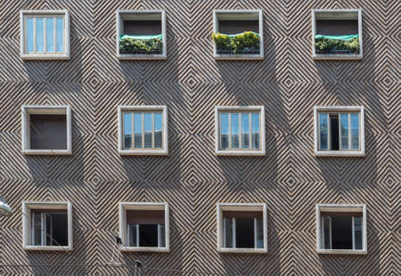 face of cement apartment building with 12 symmetrical windows in Bologna Italy