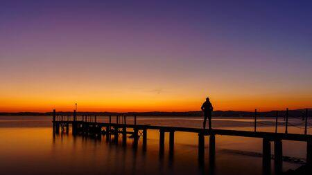 Une silhouette d'homme debout sur une jetée en bois solitaire à la mer avec un beau coucher de soleil rose. paysage marin au coucher du soleil sur une jetée en bois Banque d'images