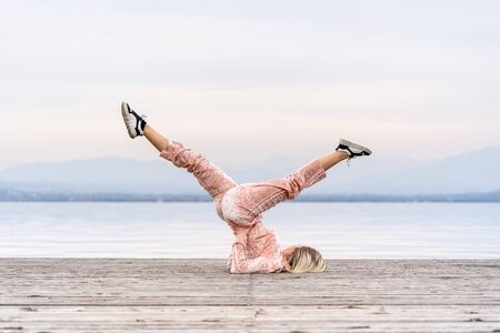 A beautiful woman performs the exercises lifting her legs to the top, lake, pier, Fitness. Sport. Yoga,