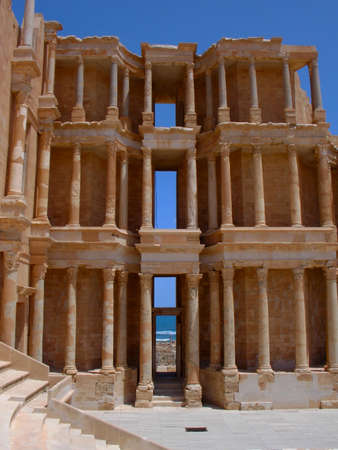 bombing: The spectacular building of the roman amphitheatre in Sabratha, an ancient roman city, in Libya, North Africa, in front of Mediterranean Sea  Stock Photo