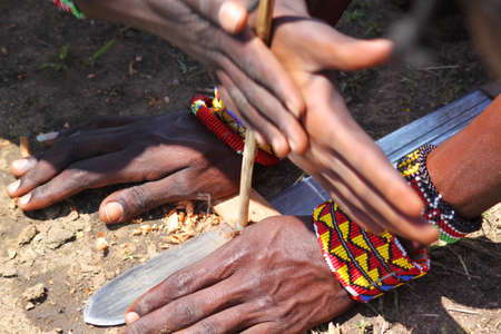 Masai Make Fire, The traditional masai method to produce fire rubbing two  pieces of wood  photo