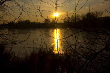 Sun is reflected across the entire width of the reservoir and forms a brilliant path.