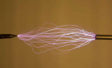 A series of spark electric discharges. Each discharge is made between the same electrodes. Discharges have different trajectories.