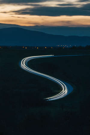 A zigzag light trail left by a car on a lonely coutryside road during sunset