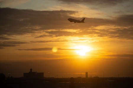 Side silhouette of airplane flying take off over a city during sunset