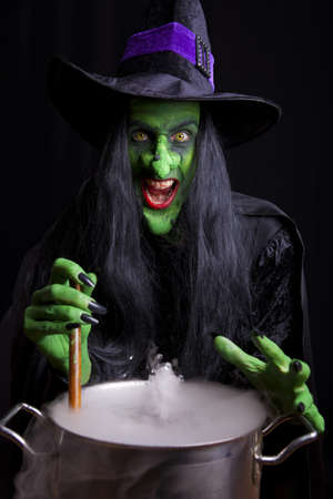wicked woman: Scary witch stirring her cauldron. Low key lighting.