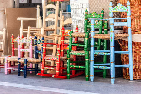 old furniture: Several wood and wicker chairs in blue, green, red and pink. They are painted floral motifs With Stock Photo