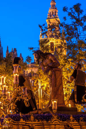 holy thursday: Float dedicated to Christ of The Cigar brotherhood. Procession to Holy Thursday. The float of Christ is in the famous tower of the Giralda? ?. The float dedicated to Christ use figures of wood to depict scenes from the Passion, and are covered in gold  Stock Photo