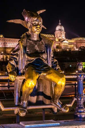 Night view of the Little Princess statue with Buda Castle in background. Budapest, Hungary