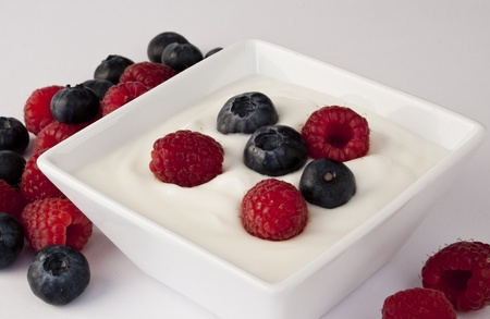White bowl of fresh yogurt with some blackberries and raspberries on the top and around the bowl in a white background