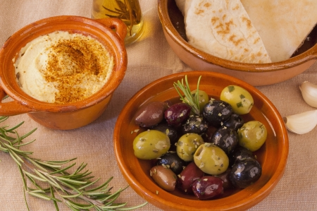 Bowl of green and black olives with a small pot of hummus and pita bread  A bottle of olive oil and a leaf of rosemary complete the image  photo