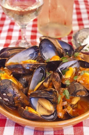 marinara: Plate of steamed mussels with tomato and white wine sauce or marinara sauce and with a glass and a bottle of white wine in the background