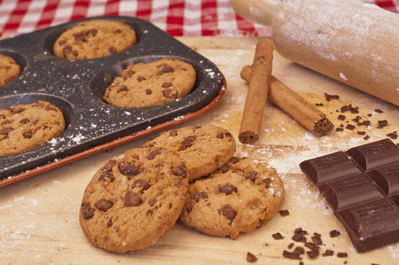 chip and pin: Baked chocolate chip cookies on a baking tray with cinnamon, chocolate and a rolling pin in the background