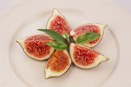 Plate of delicious cut figs with green leaves
