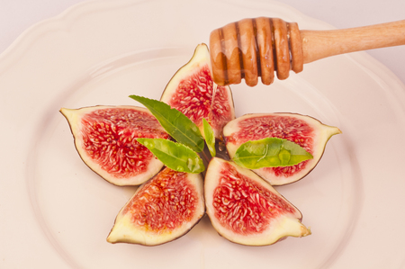 Plate of delicious cut figs with green leaves and dripping honey
