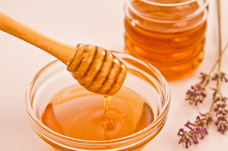 Bowl of lavender honey with wooden dipper drizzler and a jar and lavender in the background Stock Photo