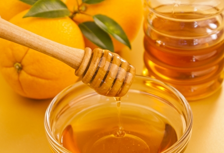 Bowl of orange honey with wooden dipper drizzler and a jar and oranges in the background Stock Photo