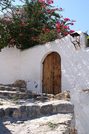 Old wooden door in a whitewashed wall in Lindos, Rhodes, Greece