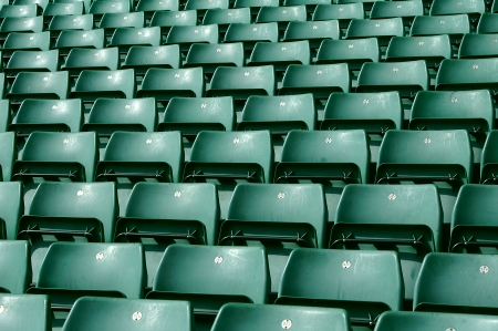 Rows of green seating in a large sports stadium