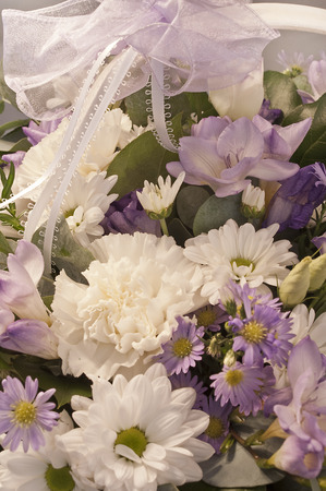 Beautiful bouquet of white, lilac and purple flowers with a lace ribbon