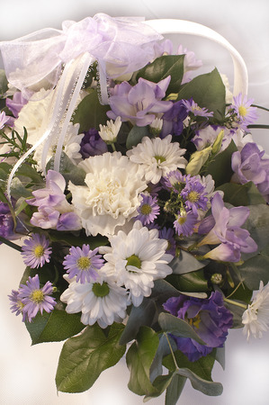 Beautiful bouquet of white, lilac and purple flowers in a basket with a lace ribbon Stock Photo