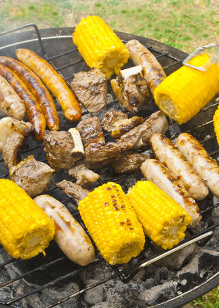 Delicious barbecue grill with beaf, sausages and corn