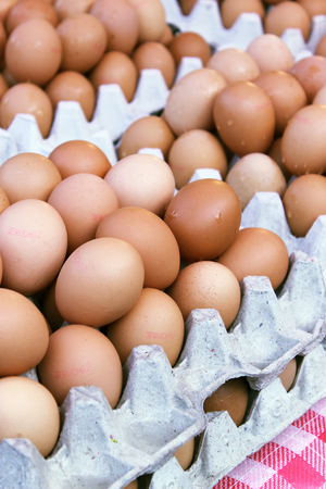 Fresh hicken eggs on sale on carton trays in a market Stock Photo