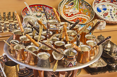 Turkish coffee pots, also know as ibrik, cezve, and briki in a street maket with ceramic bowls in the background