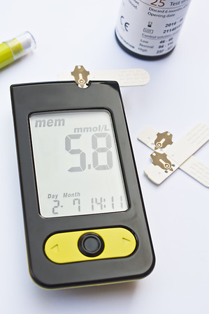 diabetes meter kit: Blood glucose monitor with a lancet, some test strips and a test strips tub in the background