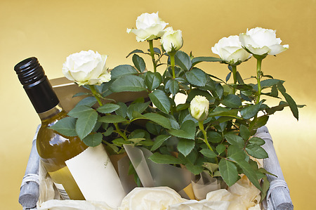 Basket with a bottle of white wine and white roses on a golden background