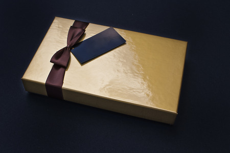 closed ribbon: Closed golden chocolate box with a brown ribbon and a black label with copy space